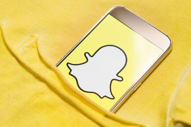 Dieses Foto zeigt ein Smartphone, auf dessen Screen großformatig der Snapchat-Geist auf gelbem Untergrund zu sehen ist.